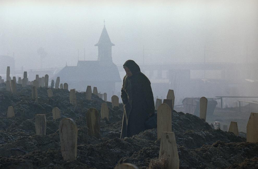 Женщина у свежих могил на кладбище в Сараево — скорбит за погибшим родственником, 17 января 1993 г. Люди ходили на кладбища ранним утром, чтобы туман мог укрыть от снайперов. © Hansi Krauss/AP