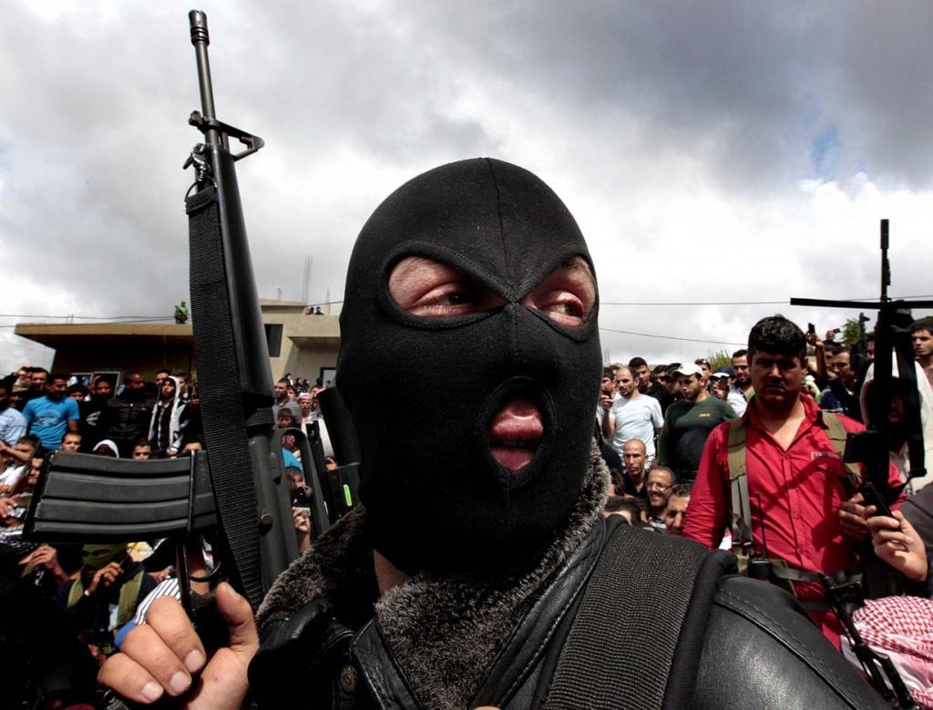 Суннитский боевик держит свое оружие на траурной процессии суннитского священнослужителя и борца с сирийским режимом Шейха Ахмеда Абдул-Вахида (Sheik Ahmed Abdul-Wahid), который был застрелен на контрольно-пропускном пункте ливанской армии в районе Аккар, на севере Ливана. (Hussein Malla/Associated Press)