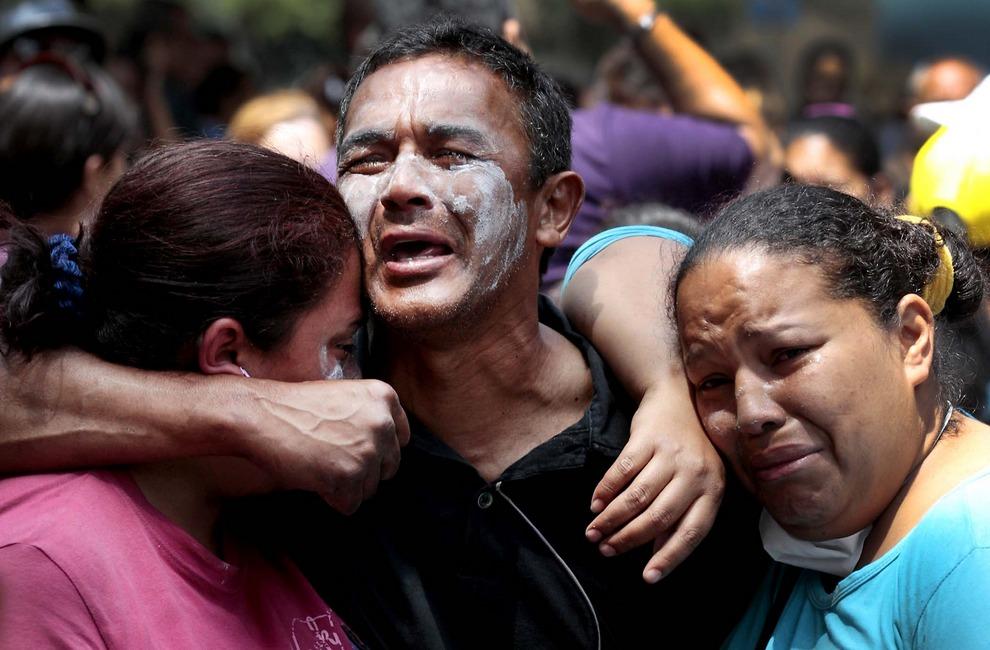 Родственники заключенных тюрьмы «Ла-Планта» обнимаются и плачут, пока войска национальной гвардии пытаются получить контроль над тюрьмой, Каракас, Венесуэла. Это случилось после того, как властям стало известно о планах масштабного побега: был обнаружен подземный туннель, который мог вывести заключеных к канализации. Белые отметины на лице человека являются ни чем иным, как зубной пастой, намазанной для ослабления эффекта слезоточивого газа. (Fernando Llano/Associated Press)