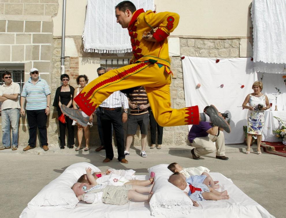 El Colacho, «Прыжки через детей». Проходит в Кастрильо-де-Мурсия, Испания. Шесть младенцев, родившихся в этом году, кладут в два ряда посреди улицы на матрасы. Потом начинают бить барабаны... и двое одетых в желто-красные наряды мужчин, вооружившись кнутами и дубинками, перепрыгивают через ни в чем неповинных крох. Считается, что этот обряд, символизирующий бегство дьявола от Святых Даров, принесет малышам силу и здоровье. (Israel Lopez)