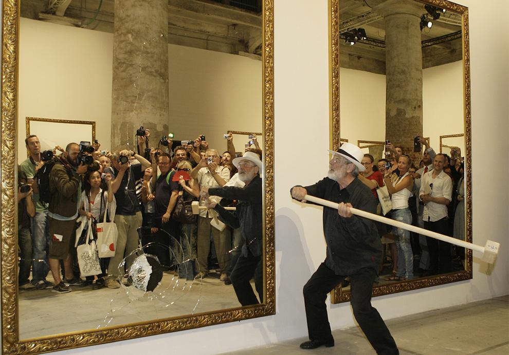 Итальянский художник Микеланджело Пистолетто (Michelangelo Pistoletto) разбивает зеркала во время своего перфоманса «22 меньше, чем 2». (AP Photo/Alberto Pellaschiar)