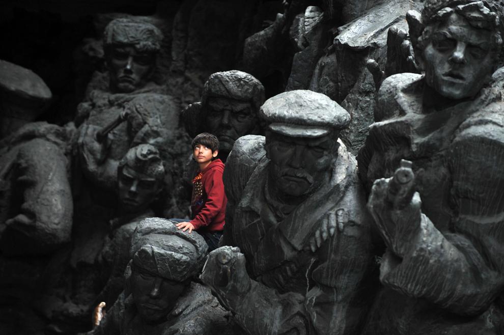 Мальчик взобрался на скульптурную композицию «Ополченцы», которая расположена на территории мемориального комплекса «Национальный Музей Истории Великой Отечественной Войны 1941-1945 годов», Город-Герой Киев, Украина, 9 мая 2012 года. (Sergei Supinsky/AFP/Getty Images)