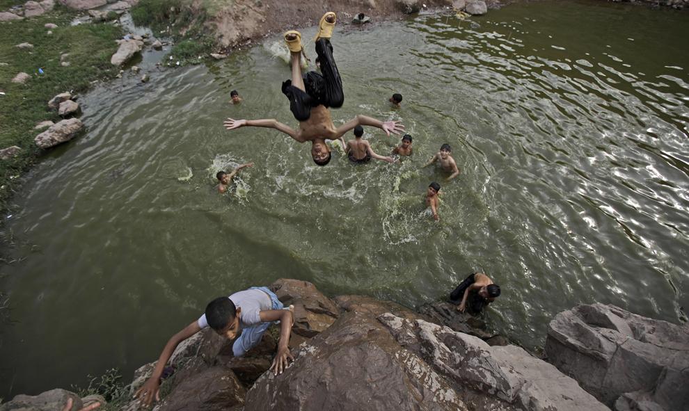 Пакистанский мальчик прыгает в ручей, чтобы освежиться, на окраине Исламабада, Пакистан, 15 мая 2012 года. (Muhammed Muheisen/Associated Press)