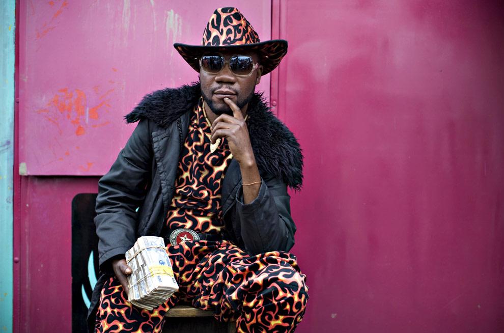 Работник обмена валют Квами Лонгэндж (Kwami Longange) позирует фотографу на углу улицы города Гома, Конго. У Квами в гардеробе насчитывается около 200 различных костюмов которые он меняет каждый день. (REUTERS/Finbarr O'Reilly)