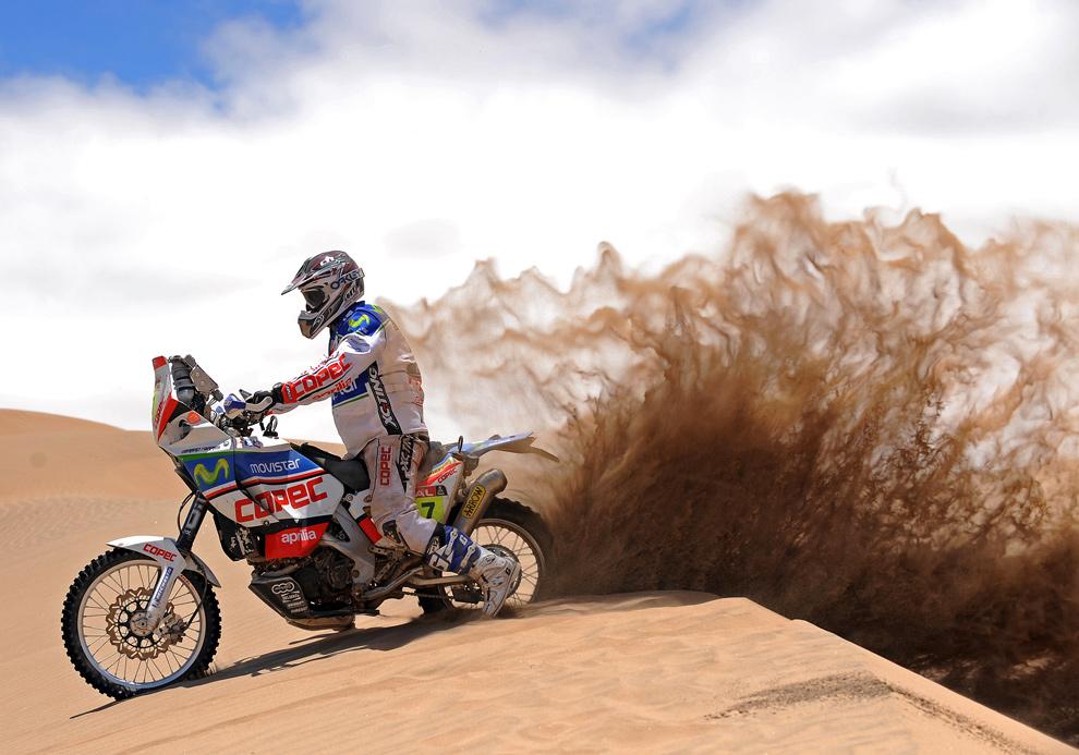 Испанец Жерар Фаррес Гуэль (Gerard Farres Guell) поднимает задним колесом своего мотоцикла Aprilia песок, четвертый этап гонок, Фиамбала, Аргентина — Копьяпо, Чили. (GABRIEL BOUYS/AFP/Getty Images)