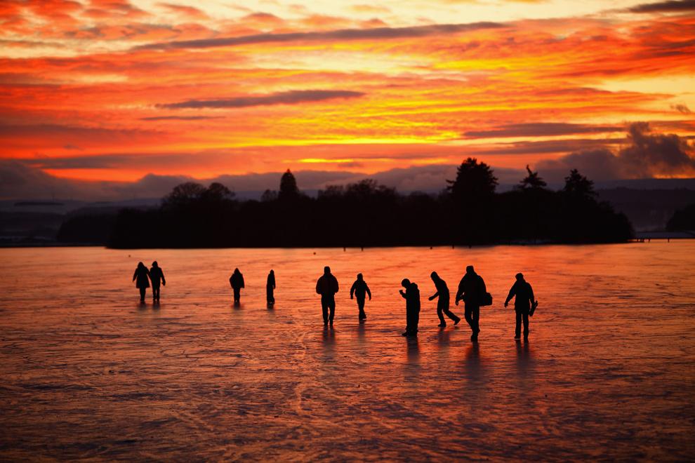 Люди гуляют вечером по замерзшему озеру Ментейт, Шотландия. (Jeff J Mitchell/Getty Images)