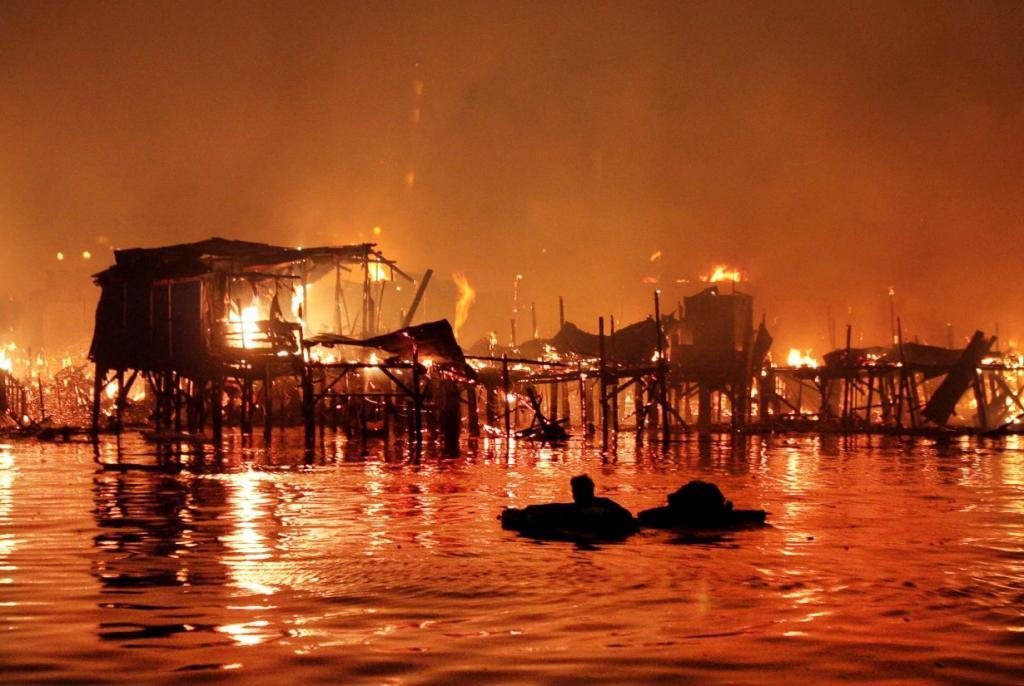 Филиппинец плавает в воде со своими вещами, пока его дом в трущобах пылает огнем, Манила, Филиппины. Чиновники утверждают, что страшнейший пожар оставил 10 000 человек бездомными. (Pat Roque / Associated Press)