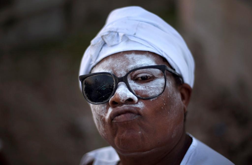 Женщина участвует в ритуале Вуду в День Мертвых на кладбище бедного района Сите-Солей в городе Порт-о-Пренс, Гаити. (AP Photo/Ramon Espinosa)