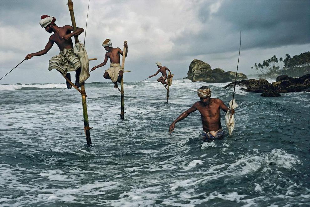 Местные рыбаки известные, как рыбаки на палках, сидят на тонких ходулях воткнутых в песок океана, в округе Коггала к югу от Галле, Шри-Ланка. (Steve McCurry)