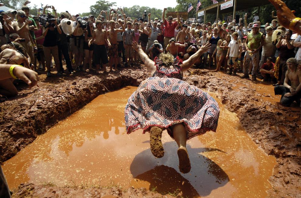 Барбара «Королева рэднеков» Бейли демонстрирует толпе, как правильно падать животом в грязь на фестивале Redneck Games в восточном Дублине, штат Джорджия, США. Бейли несколько лет подряд в 1990-е побеждала в этом соревновании. Впервые проведенные в 1996 году в качестве пародии на летние Олимпийские игры, которые состоялись в Атланте, Redneck Games включают в себя такие соревнования, как прыжки в грязь, метание туалетных стульчаков, драки за свиные ножки и другие. (Stephen Morton/Getty Images)