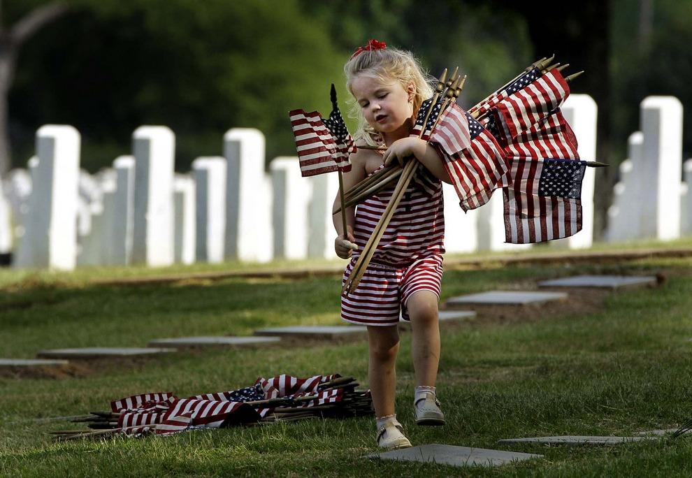 4-летняя Мадлен Грейс Уоллес (Madeline Grace Wallace) несет флажки на национальное кладбище в Литл-Роке, штат Арканзас, США, 25 мая 2012года. Девочка и ее мать посетили кладбище для того, чтобы расставить флажки на могилах в День памяти. (AP Photo/Danny Johnston)