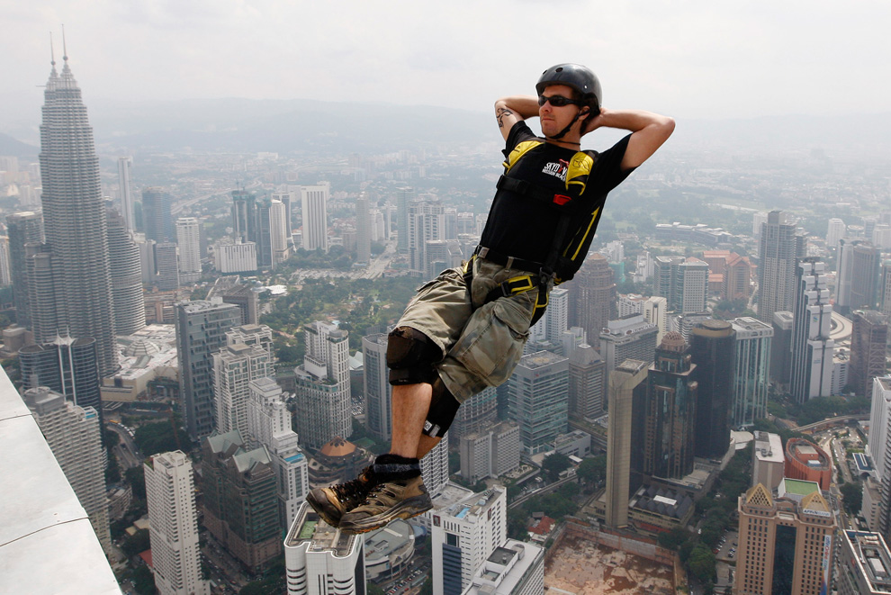 Бейс-джампер ныряет в пропасть с башни Менара Куала-Лумпур, Малайзия. Он и его коллеги пытались установить новый рекорд - каждый час в течение суток с 280 метровой башни прыгал бейс-джампер. (AP Photo/Mark Baker)