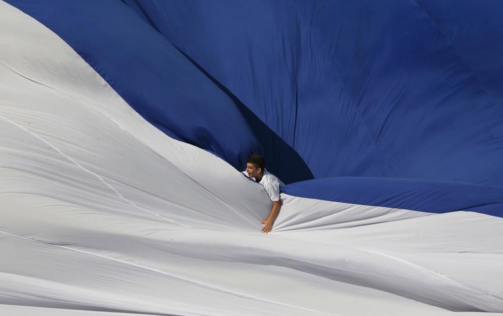 Ученик школы на фоне самого большого флага в мире, расстеленного в спорткомплексе Teddy Stadium, Иерусалим, Израиль. Его площадь — 44,404 кв. м. (AP Photo/Tara Todras-Whitehill)
