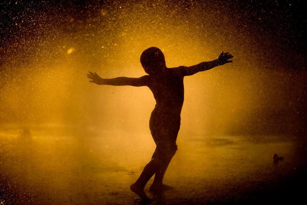 Ребенок играет в фонтане в парке в Тель-Авива, Израиль. (AP Photo/Ariel Schalit)