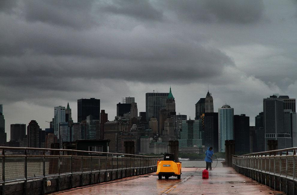 Тучи сгустились над Манхэттеном, а уборщик чистит дорогу на острове Свободы. (Kamal Sellehuddin)