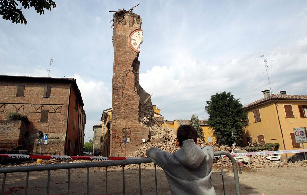 Мальчик смотрит на разрешенную башню старинного замка Делле Роше, Финале-Эмиилия. Незадолго после этого сильный подземный толчок уничтожил так же и остатки башни, которые мы видим на фото. (Reuters/Giorgio Benvenuti)