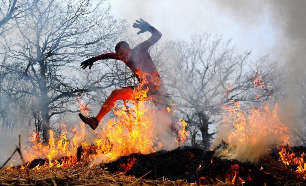 Участник гонки смело прыгает через огонь, Великобритания. (Michael Regan/Getty Images)