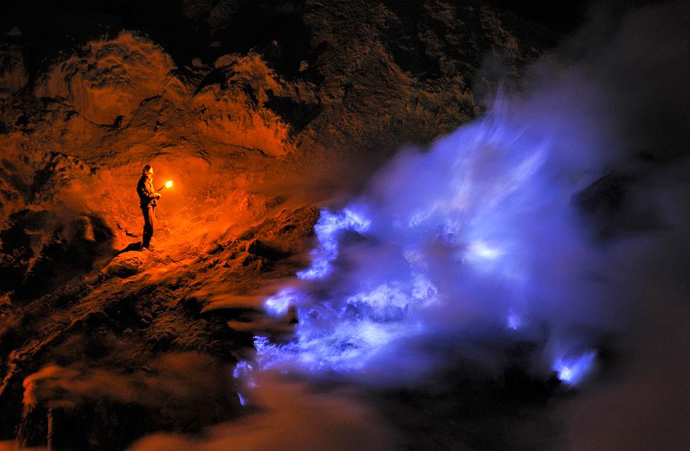 Шахтер, находясь внутри кратера вулкана Иджен, смотрит на поток жидкой серы, который горит синим пламенем, остров Ява, Индонезия. (Olivier Grunewald)