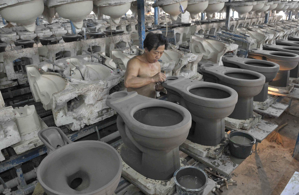 Мужчина в процессе изготовления унитазов на экспорт, керамическая фабрика в Таншане, Хубэй. Китай. (REUTERS/Stringer)