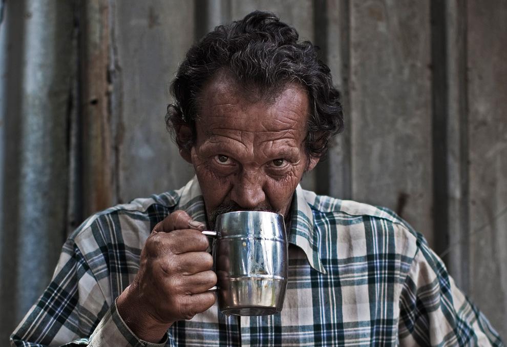 57-летний Андре Кутзее (Andre Coetzee) пьет утренний кофе в лагере для бедных белых южноафриканцев в городе Крюгерсдорп, Южно-Африканская Республика. После мирового экономического кризиса для многих белых наступили тяжкие времена. (REUTERS/Finbarr O'Reilly)