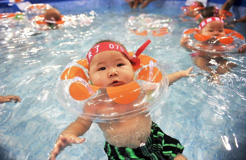 Китайские малыши плескаются в бассейне под строгим контролем своих родителей в рамках соревнования по плаванию, проводимого с целью установить мировой рекорд по количеству плавающих одновременно детей в одном бассейне. (STR/AFP/Getty Images)