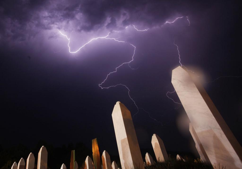 Молнии сверкают над Мемориальным центром накануне массовых захоронений в Потокари близ Сребреницы, Босния. Тела 520 недавно идентифицированных жертв резни в Сребренице будут похоронены 11 июля, в 17-ю годовщину массового убийства 8 тыс. мусульман силами боснийских сербов под командованием Ратко Младича. (REUTERS/Dado Ruvic)