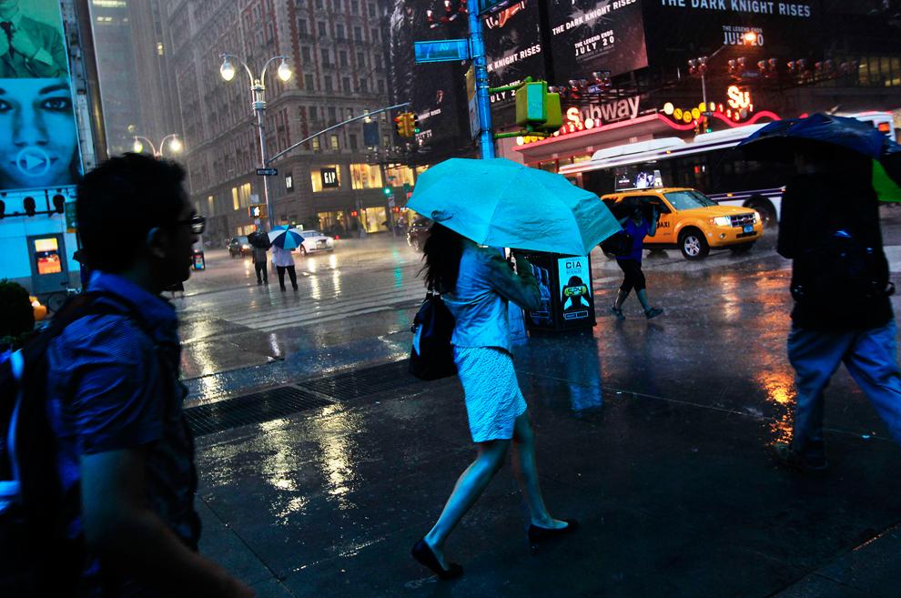 Люди идут по Таймс-Сквер во время сильного дождя в Нью-Йорке, США, 18 июля 2012 года. (Shannon Stapleton/Reuters)
