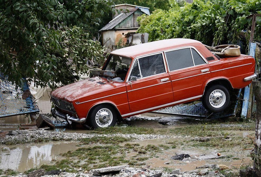 Уничтоженный автомобиль стоит на затопленной улице в результате наводнения в городе Крымске, Россия, 7 июля 2012 года. (REUTERS/Vladimir Anosov)