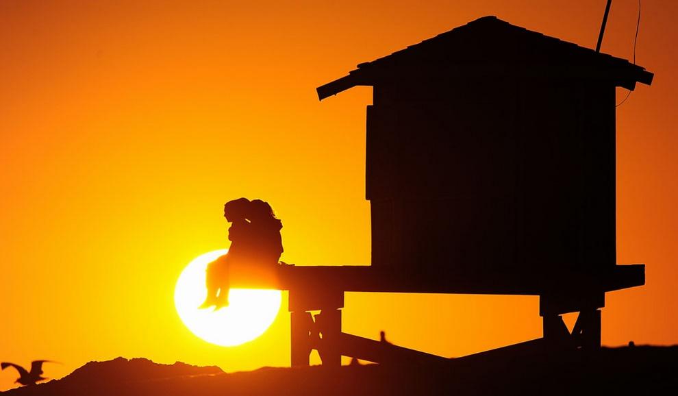 Люди наслаждаются закатом, Сил-Бич, Калифорния США, 9 июля 2012 года. (Frederic J. Brown/AFP/Getty Images)