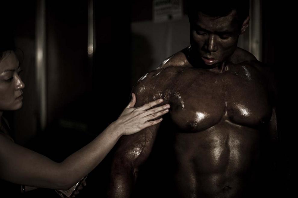Девушка намазывает маслом одного из участников соревнования. (Philippe Lopez/Getty Images)