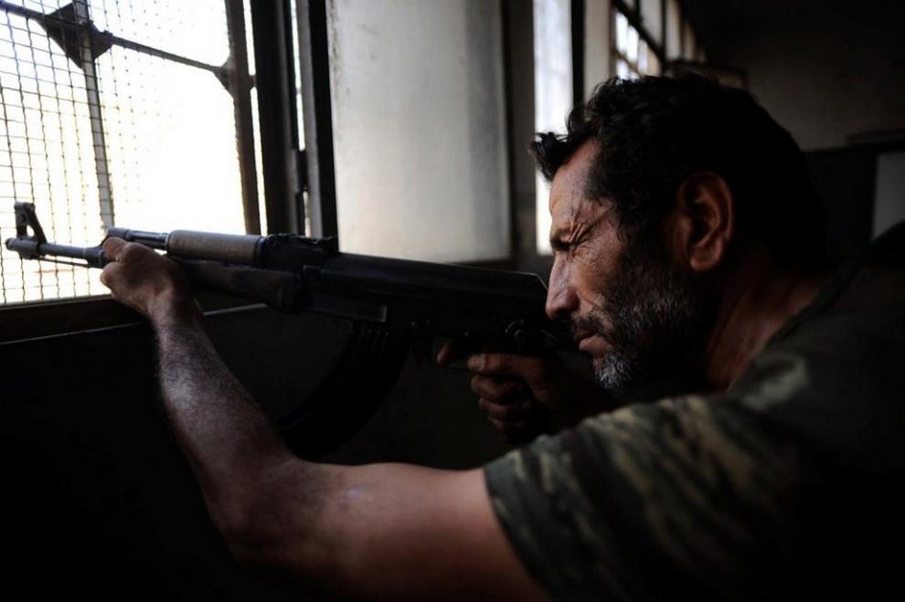 Мужчина прицелившись, сидит у окна в здании начальной школы близ города Алеппо, Сирия, 30 июля 2012 года. (EPA)