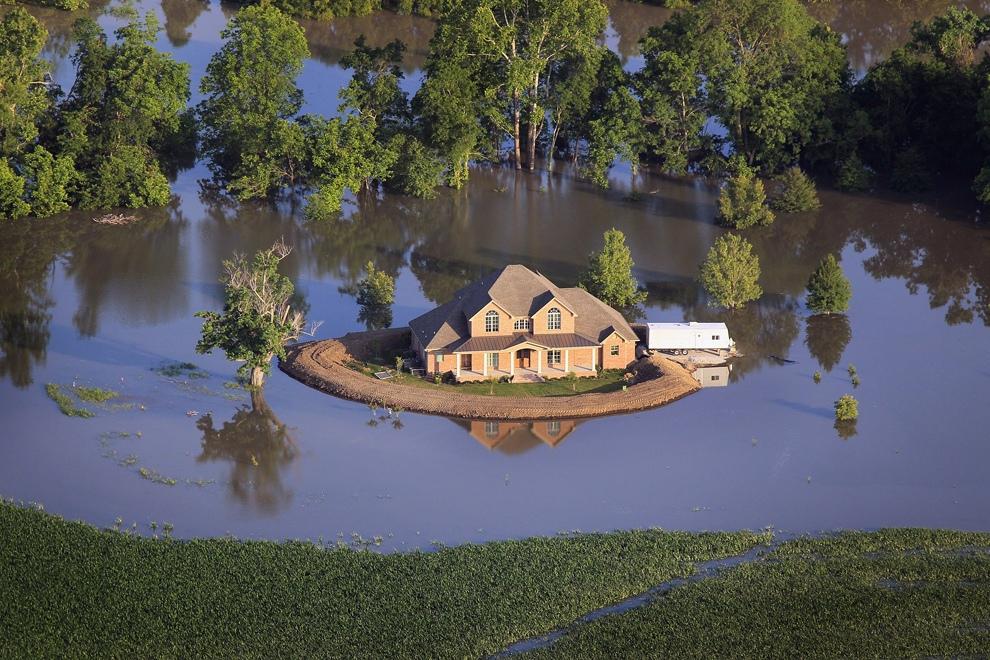 Дамба защищает дом, окруженный паводковыми водами из реки Язу, штат Миссисипи, США. Вышедшая из берегов река Миссисипи повышает уровень реки Язу, вызвав