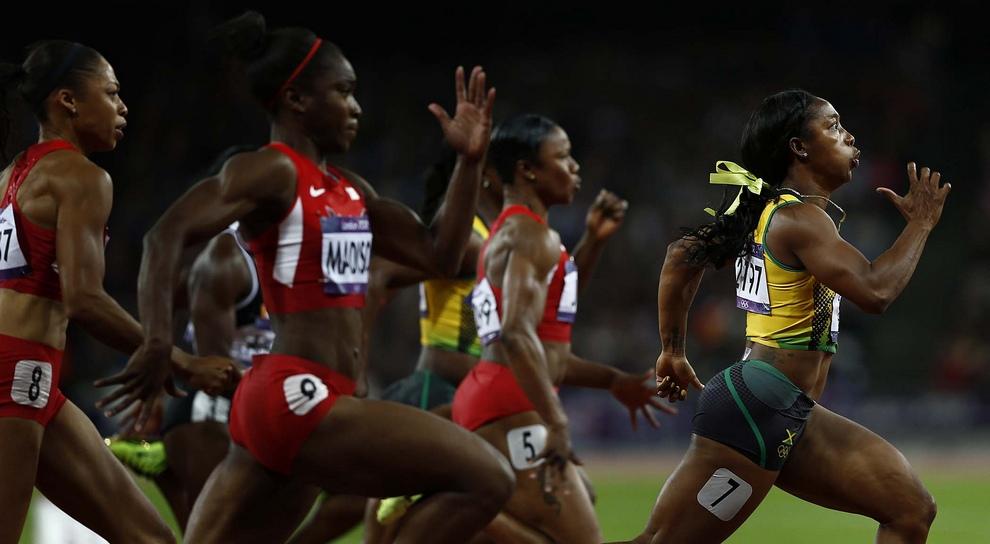 Ямайская бегунья Шелли-Энн Фрейзер-Прайс (справа) что есть силы мчит к своей очередной золотой медали в финале забега на 100 метров. (AP Photo/Daniel Ochoa De Olza)