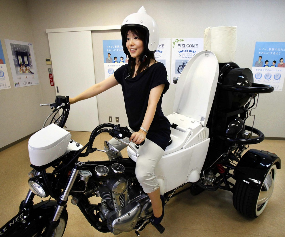 Сотрудница японского производителя туалетов TOTO Акико Матсуяма (Akiko Matsuyama) позирует на трехколесном мотоцикле Toilet Bike Neo, Фудзисава, Токио, Япония. Продукты жизнедеятельности водителя затем используются в качестве биотоплива. (AP Photo/Koji Sasahara)