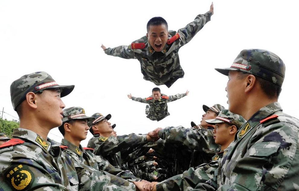 Военные полицейские прыгают на руки своих товарищей по оружию во время психологических тренингов, Тунлин, провинция Аньхой, Китай. (REUTERS/China Daily)