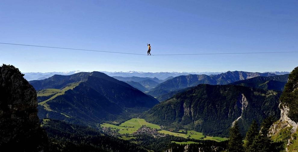 Канатоходец у горы Вендельштайн в Баварских Альпах, Байришцелль, Германия. Он привязан веревкой безопасности, но должен самостоятельно преодолеть 70 метров на высоте 1,8 км. (Uwe Lein/dapd)