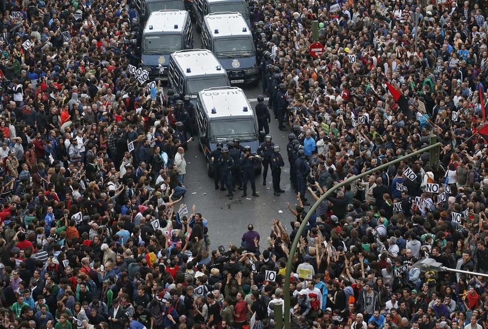 Демонстранты окружают полицейских во время многотысячного митинга у здания испанского парламента, Мадрид, Испания. (REUTERS/Andrea Comas)