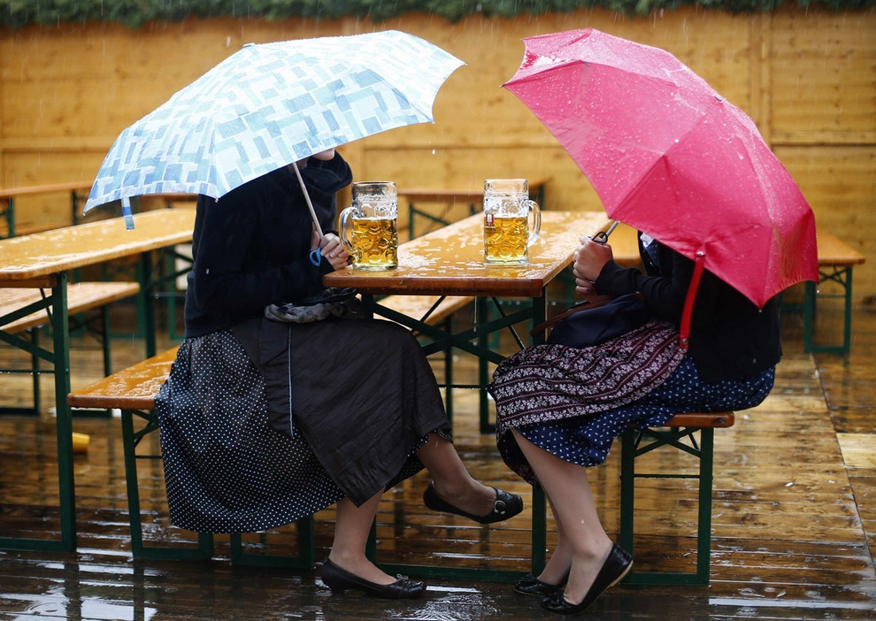"Revellers sit under umbrellas with their traditional one-litre ""Masskrug"" beer mugs on a beer garden table during heavy rain falls at  the opening day of the Munich Oktoberfest at the Theresienwiese in Munich, September 22, 2012. The world's biggest beer festival runs until October 7.  REUTERS/Kai Pfaffenbach (GERMANY - Tags: SOCIETY ENTERTAINMENT) ORG XMIT: KAI23"