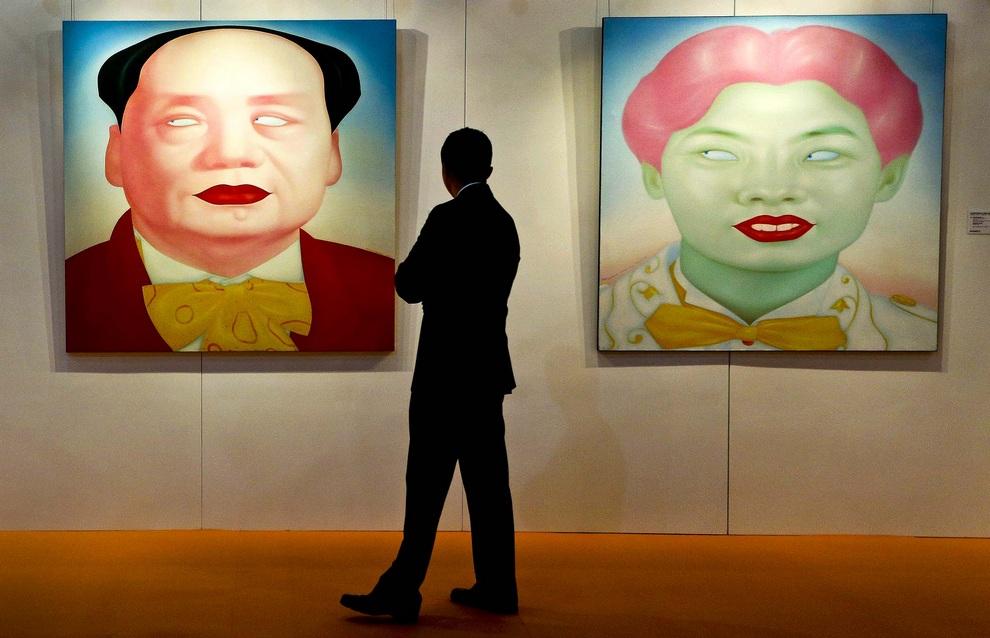 Посетитель предаукционной выставки Sotheby's в Гонконге рассматривает две картины современного художника Фэна Чжэнцзе (Feng Zhengjie) — «Мао» (слева), ценой $32 300, и «Серия китайских портретов № 12», ценой $45 200. (AP Photo/Vincent Yu)