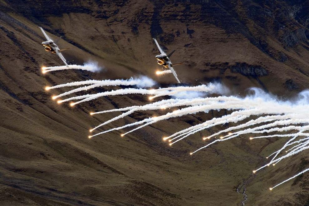 Истребители F/A-18 «Хорнет» выпускают сигнальные огни во время демонстрационного полёта возле базы ВВС Швейцарии в Бернских Альпах, Швейцария. (FABRICE COFFRINI/AFP/Getty Images)