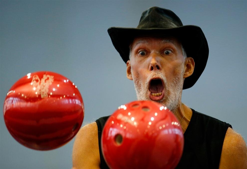 Словак Милан Роскопф (Milan Roskopf) пытается побить мировой рекорд по жонглированию шарами для боулинга, фестиваль рекордов «Вызов невозможности», Будаёрш, Венгрия. (REUTERS/Laszlo Balogh)