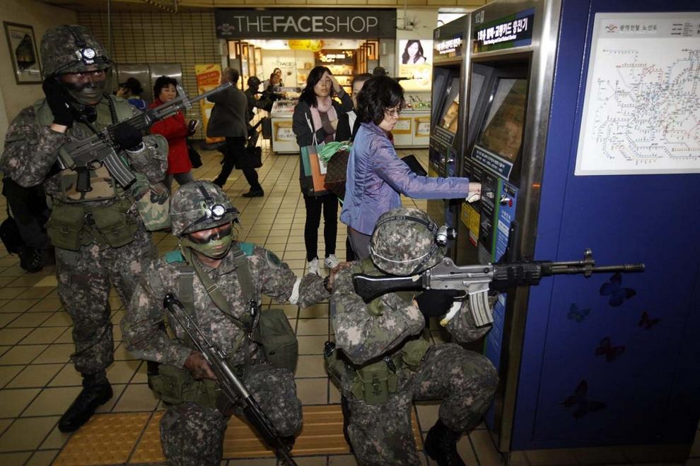 Оперативники занимают позицию у торгового автомата. Женщины в очереди не обращают на это ни малейшего внимания. (REUTERS/Kim Hong-Ji)