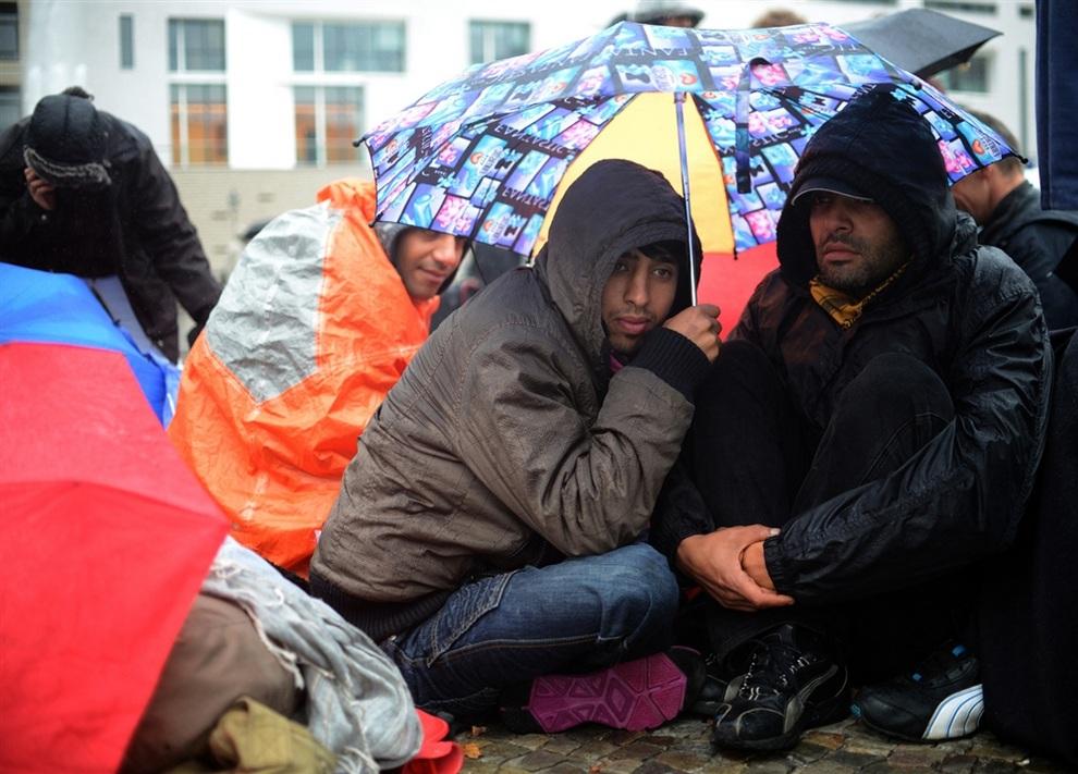 Устроившие голодовку беженцы скрываются от дождя под зонтами в центре Берлина, Германия. (JOHANNES EISELE/AFP/Getty Images)