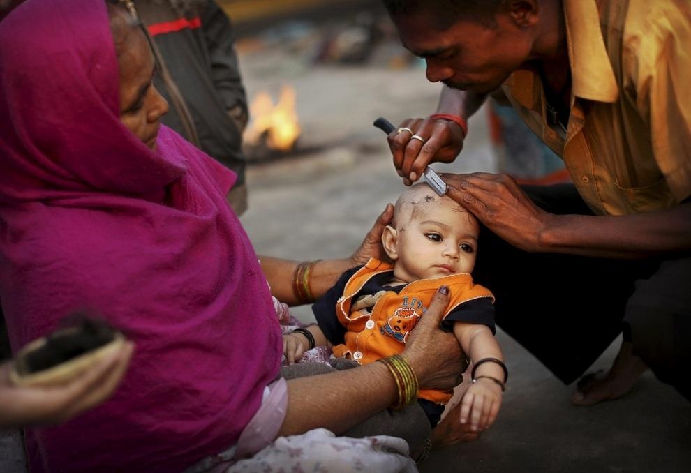 Парикмахер стрижет ребенка у реки Джамна в Нью-Дели, Индия. (AP Photo/Kevin Frayer)