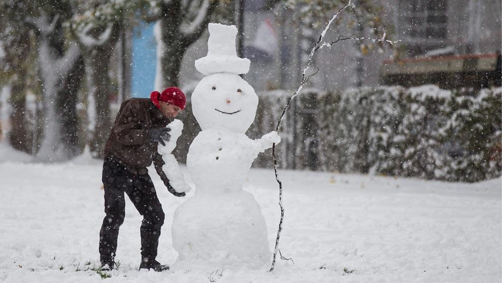 Мужчина лепит снеговика, Швейцария. (EPA/ИТАР-ТАСС)