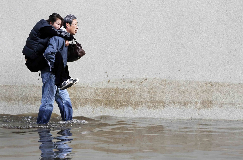 Мужчина несет свою жену по затопленной улице Хобокена, штат Нью-Джерси, США. Количество жертв от урагана «Сэнди» достигло 45 человек. Главной причиной смертей стали затопленные улицы, падающие деревья и неосмотрительность людей. (REUTERS/Gary Hershorn)