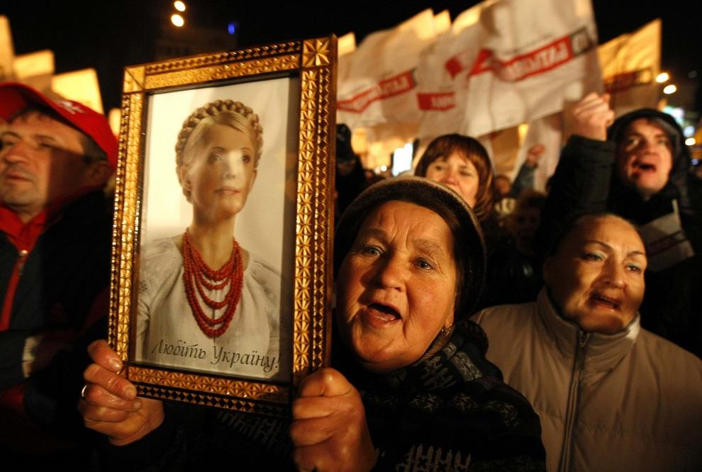 Сторонница партии «Батькивщина» держит портрет Юлии Тимошенко во время митинга оппозиции у здания ЦИК в Киеве, Украина. (REUTERS/Anatolii Stepanov)
