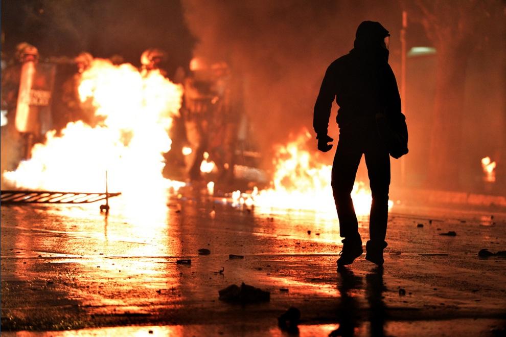Бесстрашный парень в маске идет по горящей улице на ряды полицейских близ здания парламента, Афины, Греция. (ARIS MESSINIS/AFP/Getty Images)