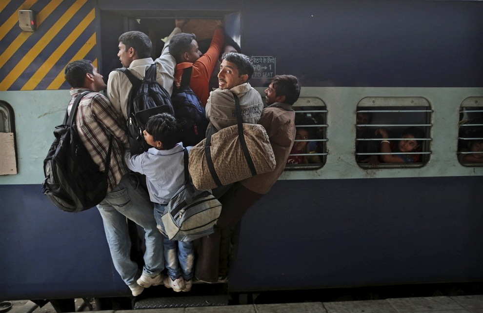 Индусы пытаются пропихнуться в вагон поезда, направляющегося в штат Бихар, Нью-Дели, Индия. (AP Photo/Kevin Frayer)
