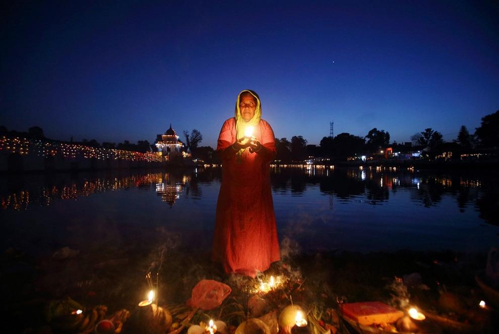 Верующая стоит посреди реки со свечей руках, посылая молитвы богу солнца Сурье, Катманду, Непал. (REUTERS/Navesh Chitrakar)